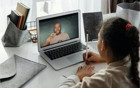 man teaching girl through computer screen