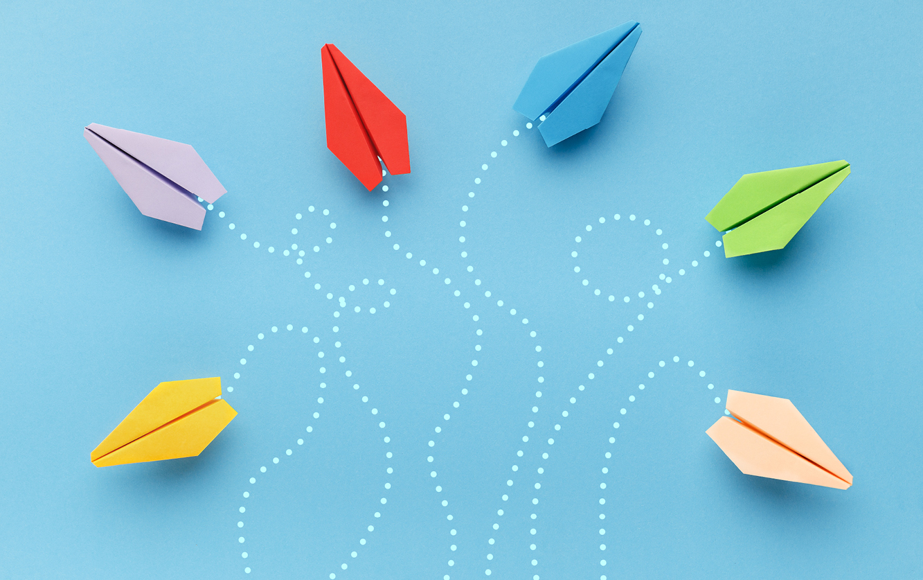 several colourful paper airplanes on different paths